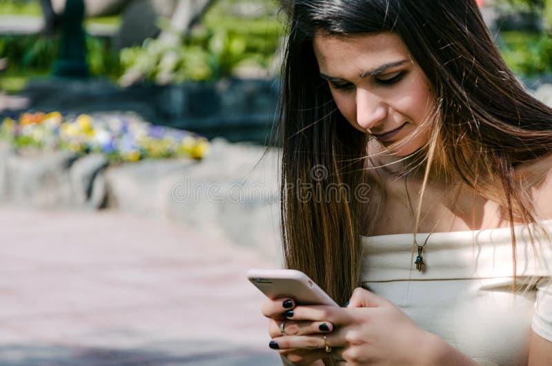 Meios de observação da menina feliz em um smartphone que senta-se em um banco de um parque fotos de stock
