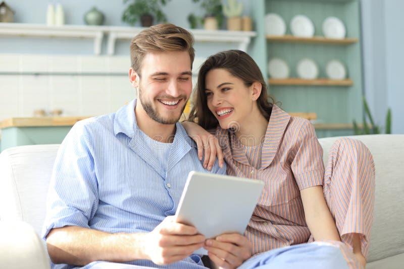 Meios de observa??o dos pares novos satisfeitos em linha em uma tabuleta que senta-se em um sof? na sala de visitas fotografia de stock royalty free