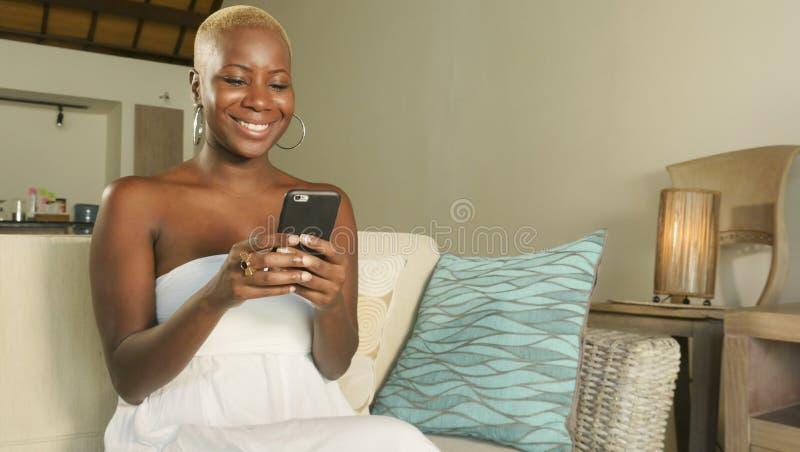 meios sociais de utilização entusiasmado de sorriso novos app do Internet da mulher americana bonita e feliz do africano negro em fotografia de stock