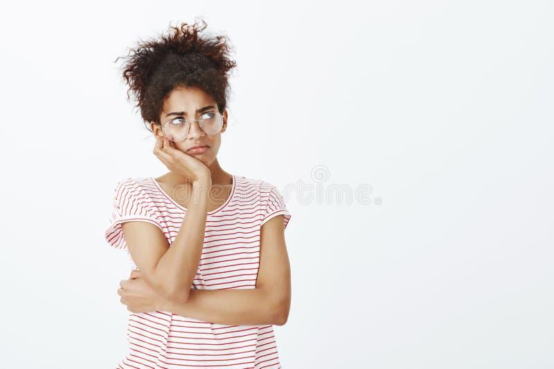 Meisje aan heimwee lijdend en bored feleing Portret van sombere leuke vrouw in glazen en gestreepte t-shirt, leunend hoofd op han stock fotografie
