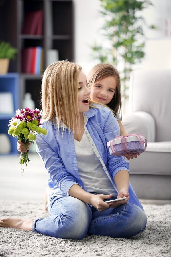 Meisje aanwezige geven aan haar moeder thuis royalty-vrije stock foto