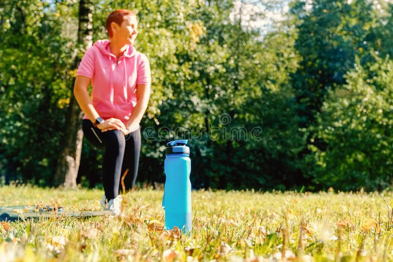 Meisje in aard voor sportieve gebeurtenissen De fles van het sportenwater Gezonde Levensstijl stock foto