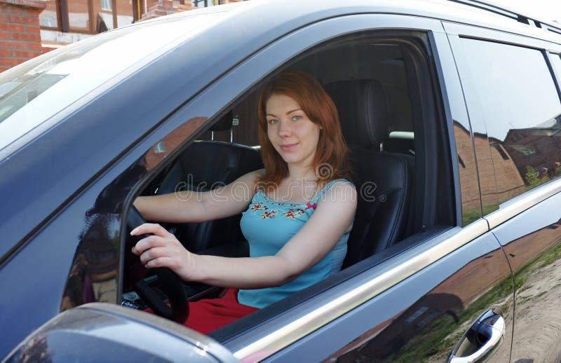 Meisje achter het stuurwiel van een auto. stock afbeelding