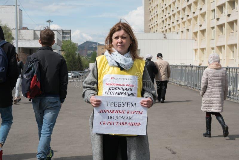 Meisje-activist die zich in het piket met aanplakbiljetten met de inschrijving bevinden: bedrogen onroerende goedereninvesteerder royalty-vrije stock foto's