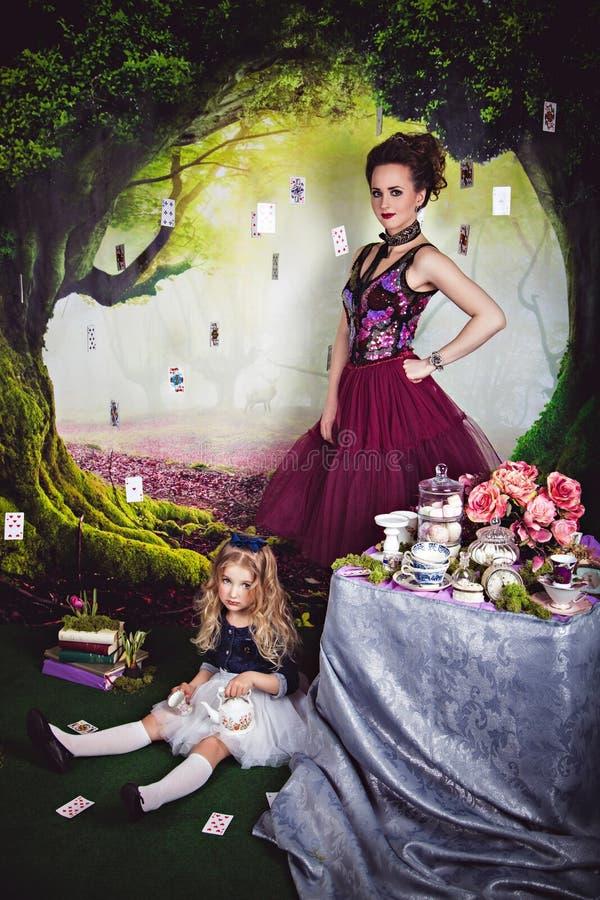 Meisje als Alice in Sprookjesland en kwade koningin stock foto's