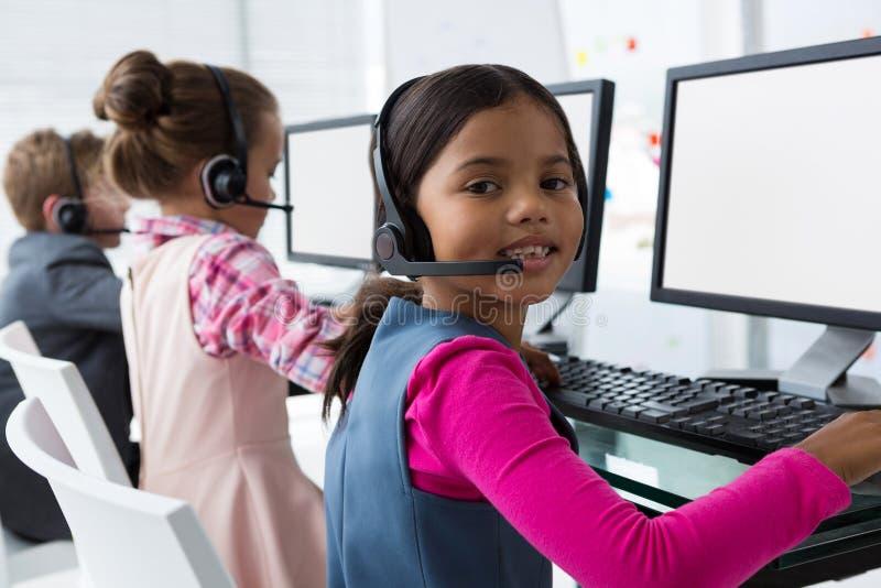 Meisje als klantenzorg het uitvoerende glimlachen terwijl het werken in het bureau royalty-vrije stock afbeelding