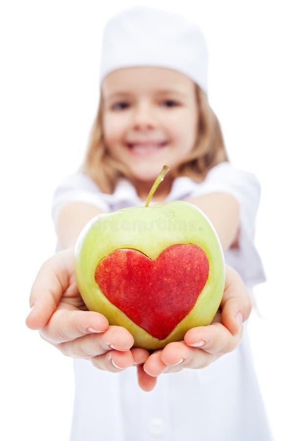 Meisje als verpleegster die u een appel geeft stock afbeelding