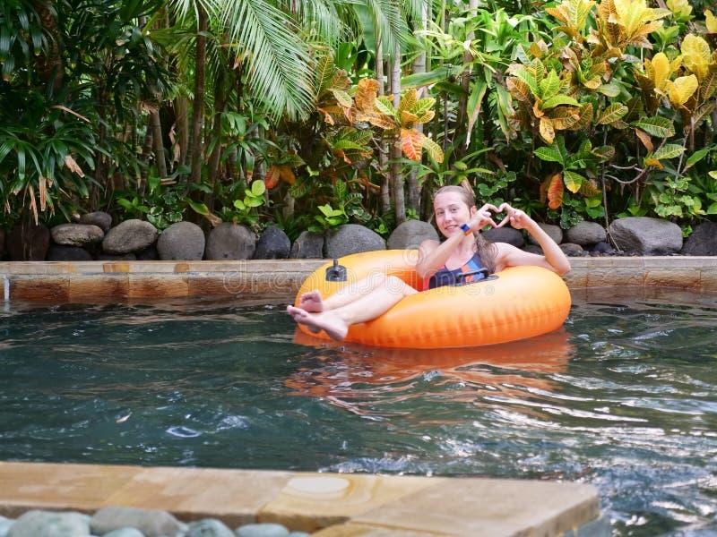 Meisje in aquapark op een opblaasbaar stuk speelgoed stock afbeelding