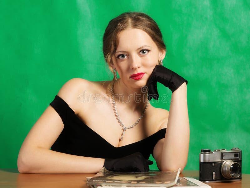 Meisje in avondjurkzitting bij lijst met tijdschriften royalty-vrije stock foto