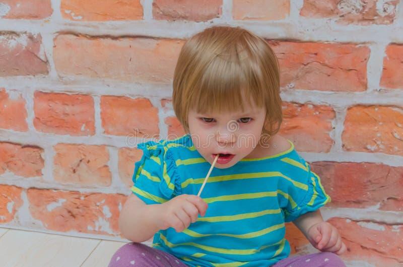 Meisje, baby met suikergoed op stok, op bakstenen muurachtergrond stock afbeeldingen