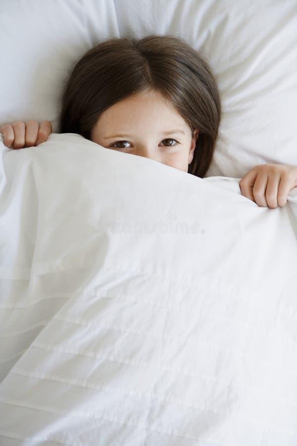Meisje in Bed die Deken over Gezicht trekken royalty-vrije stock afbeeldingen