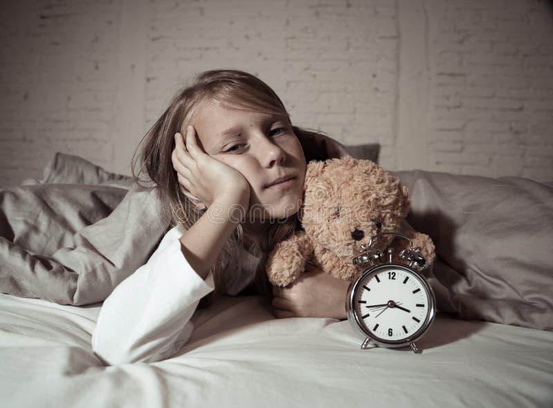 Meisje in bed wakker bij nacht die en rusteloze tonende klok voelen kan zij niet slapen geeuwen stock afbeeldingen