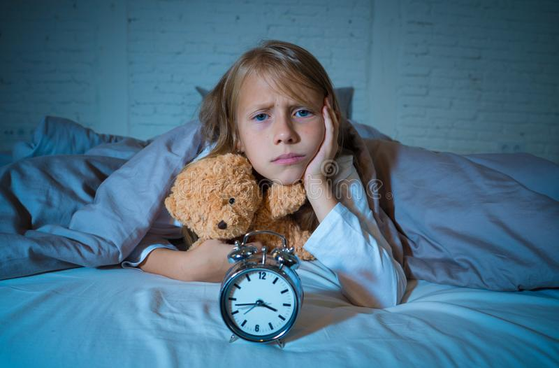 Meisje in bed wakker bij nacht die en rusteloze tonende klok voelen kan zij niet slapen geeuwen stock foto