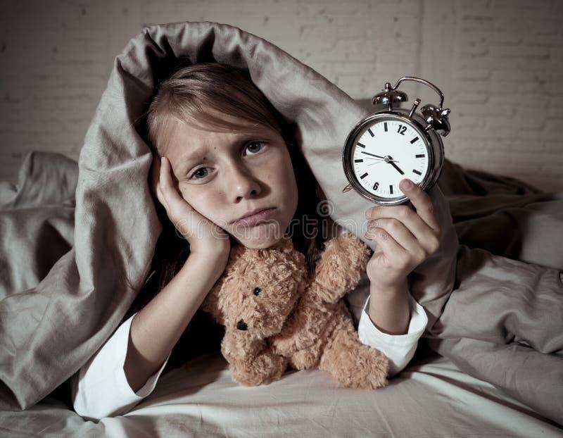 Meisje in bed wakker bij nacht die en rusteloze tonende klok voelen kan zij niet slapen geeuwen stock afbeelding