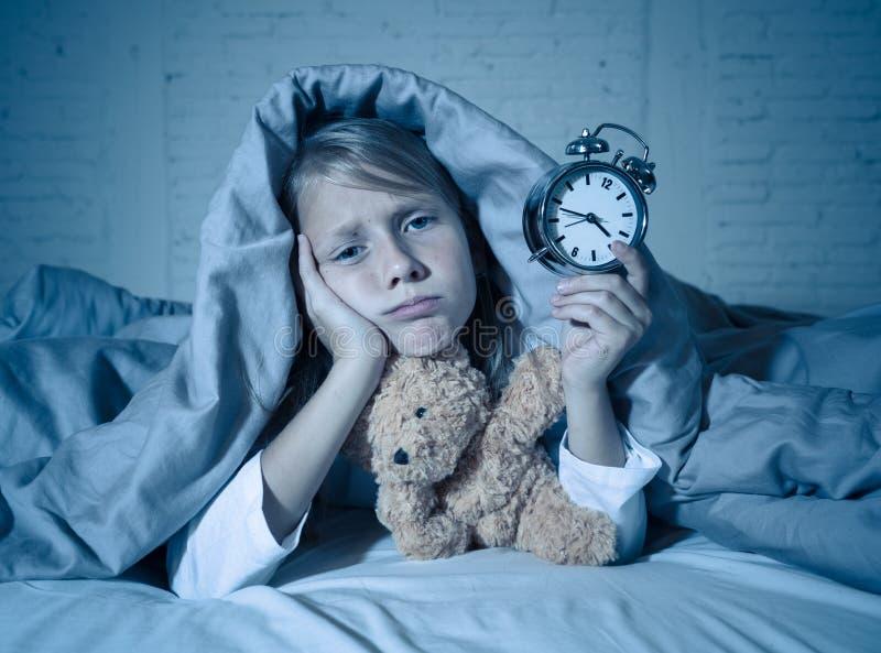 Meisje in bed wakker bij nacht die en rusteloze tonende klok voelen kan zij niet slapen geeuwen royalty-vrije stock foto