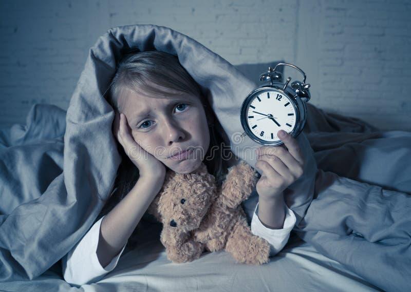 Meisje in bed wakker bij nacht die en rusteloze tonende klok voelen kan zij niet slapen geeuwen royalty-vrije stock foto's