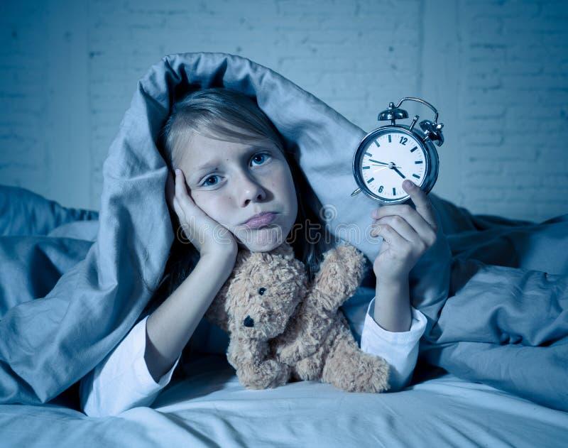 Meisje in bed wakker bij nacht die en rusteloze tonende klok voelen kan zij niet slapen geeuwen royalty-vrije stock afbeeldingen