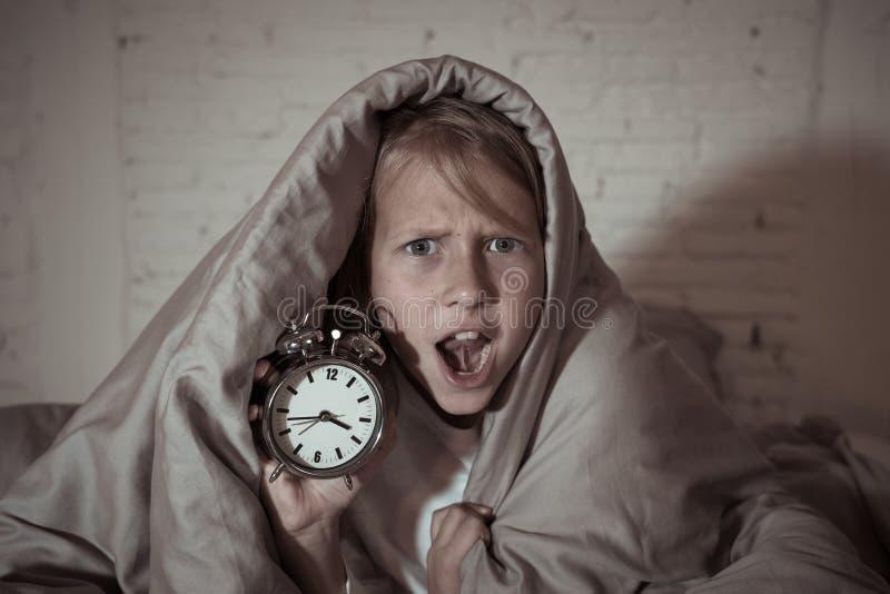 Meisje in bed wakker bij nacht die en rusteloze tonende klok voelen kan zij niet slapen geeuwen royalty-vrije stock fotografie