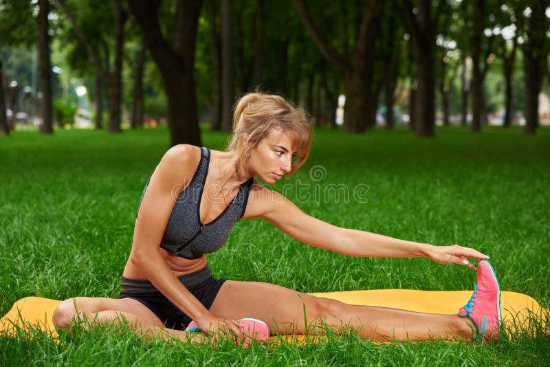 Meisje belast met geschiktheid en gymnastiek in het park stock foto