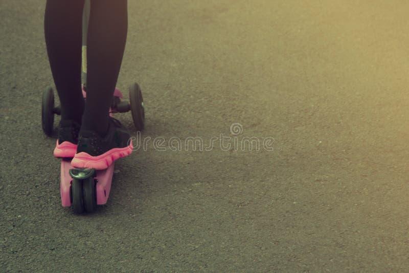 Meisje berijdende autoped in het park Onderwijs, ouderschapconcept De ruimte van het exemplaar stock afbeeldingen