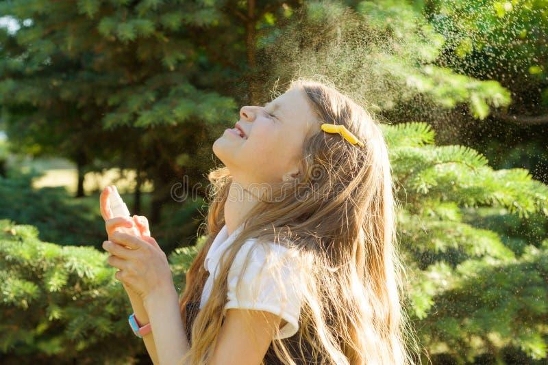 Meisje bespuitend gezicht met thermisch water Vreugde en plezier op een hete zonnige dag stock foto