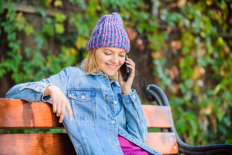 Meisje bezig met achtergrond van de smartphone de groene aard Vrouw die mobiel gesprek hebben De vraagvriend van meisjessmartphon stock fotografie