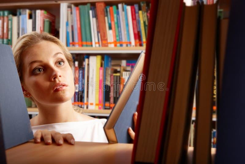 Meisje in bibliotheek stock foto's