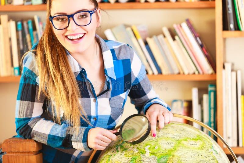 Meisje in bibliotheek met bol en vergrootglas stock afbeelding