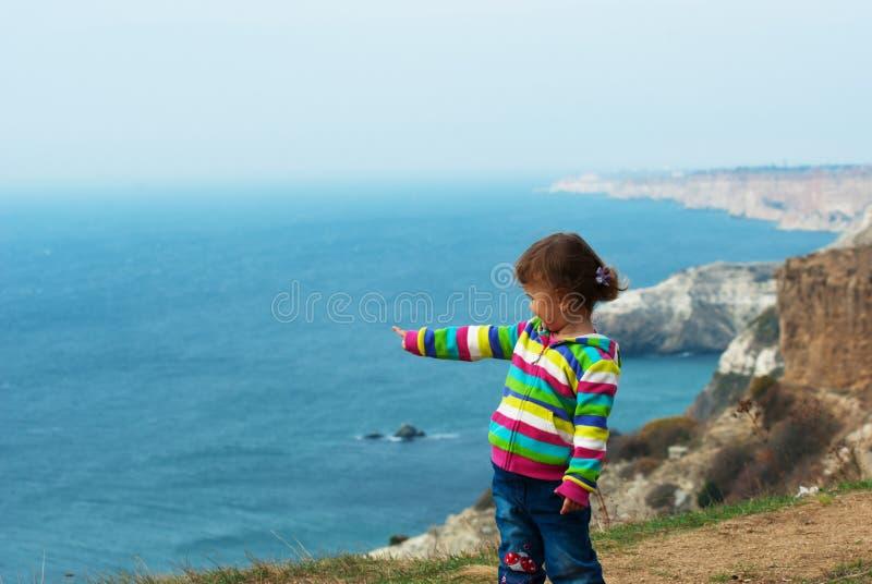 Meisje bij de klip aan het overzees royalty-vrije stock afbeelding