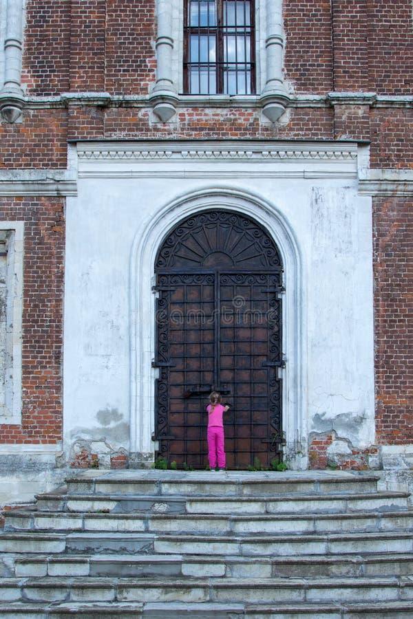 Meisje bij de reusachtige metaaldeuren aan tempel stock afbeelding
