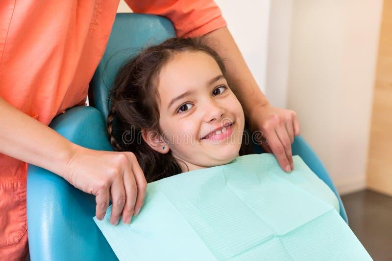 Meisje bij de tandarts die voor de behandeling voorbereidingen treffen stock foto