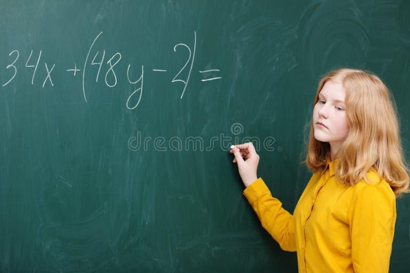meisje bij het bord in een wiskundeklasse stock fotografie