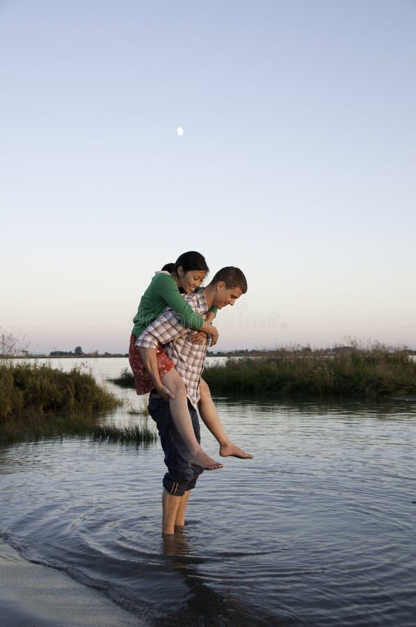 Meisje bij jongens de achter status in water stock foto's