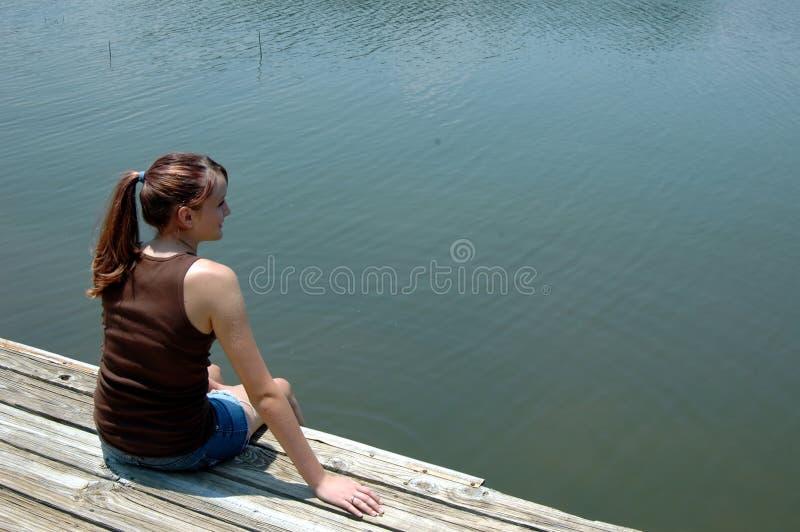 Meisje bij meer op dok stock fotografie