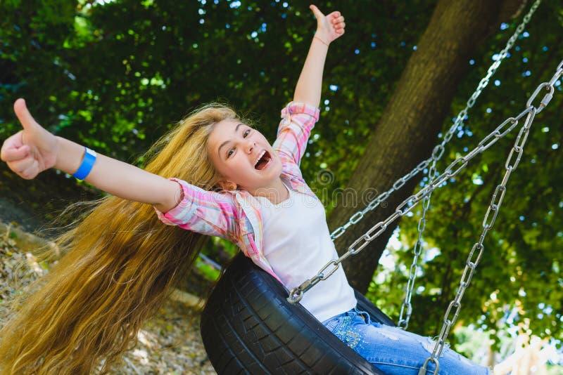 Meisje bij speelplaats Kind het spelen in openlucht in de zomer Tiener op een schommeling royalty-vrije stock afbeelding