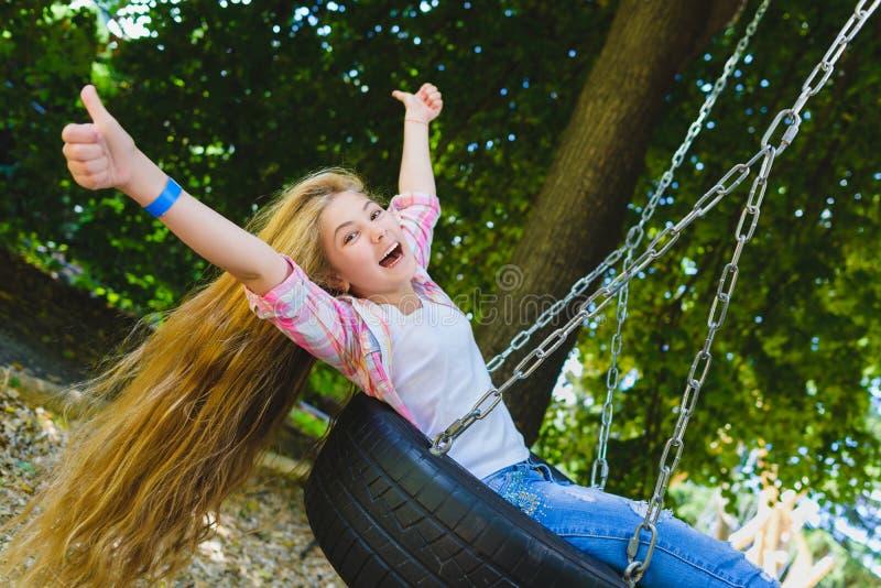 Meisje bij speelplaats Kind het spelen in openlucht in de zomer Tiener op een schommeling stock afbeelding