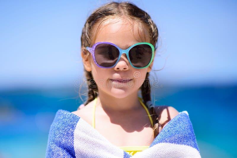 Meisje bij tropisch die strand met handdoek wordt behandeld stock afbeelding