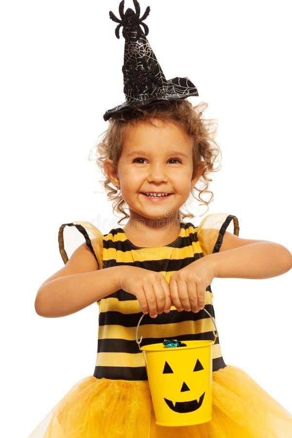 Meisje in bijenkostuum met Halloween-emmer stock afbeelding