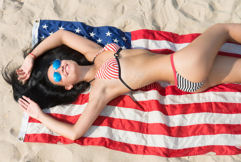 Meisje in bikini en het liggen op de Amerikaanse vlag stock foto