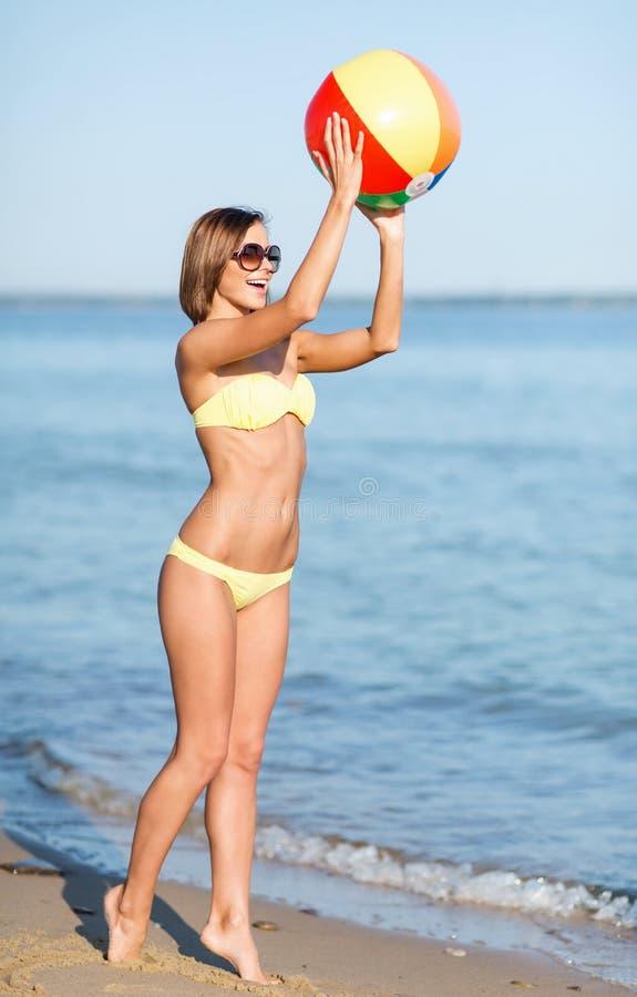 Meisje in bikini het spelen bal op het strand stock afbeelding