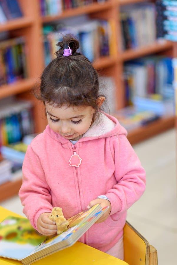 Meisje binnen in Front Of Books Leuk Jong Peuterspel met Stuk speelgoed en Lezingsboek Bibliotheek, Winkel, die in Huis opschort royalty-vrije stock afbeelding