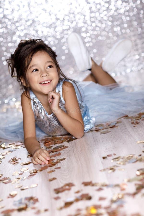 Meisje in blauwe kledingszitting op de vloer met confettien stock afbeelding