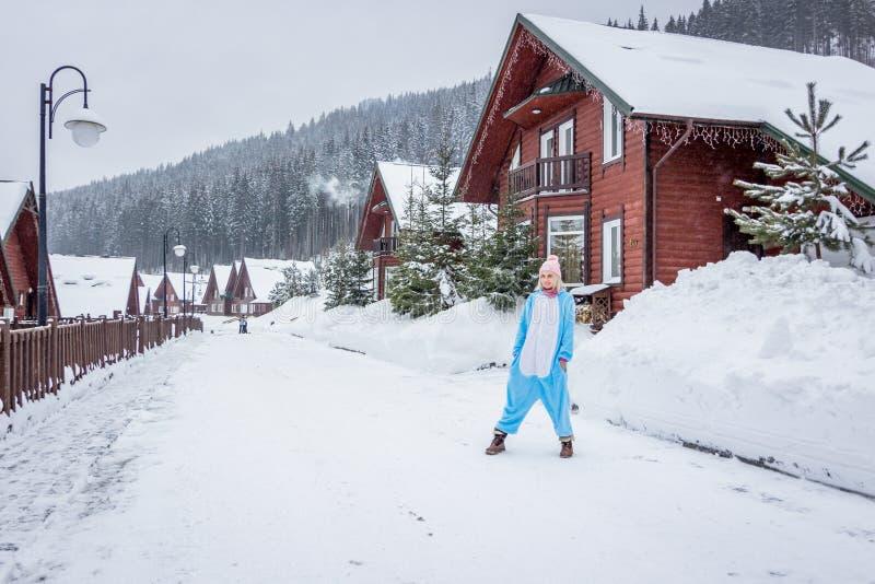 Meisje in blauwe, roze kigurumi van eenhoornpijama openlucht voor de houten huizen op het skirapport in sneeuwbergen stock foto's