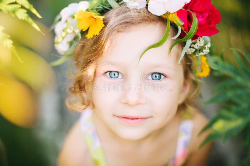 Meisje in bloemkroon in de tuin stock afbeeldingen