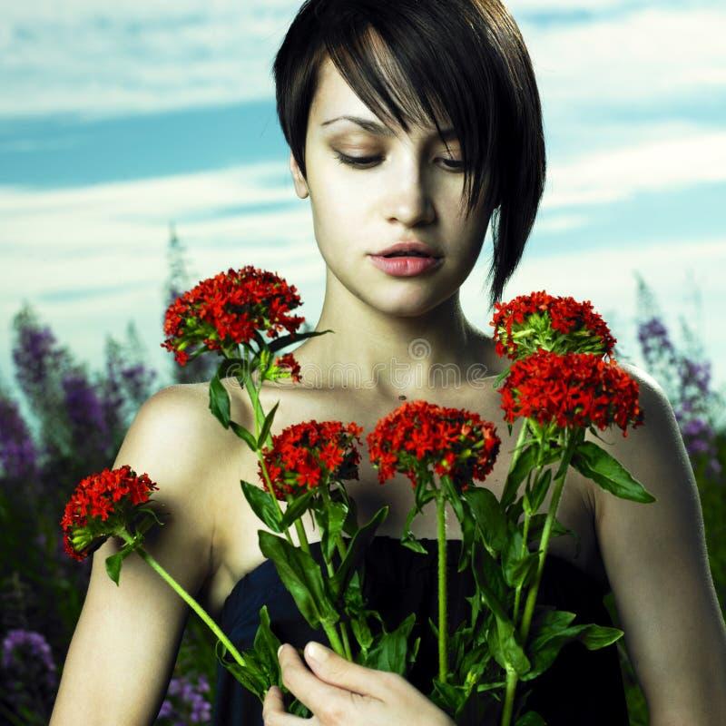 Meisje in bloemweide royalty-vrije stock afbeelding