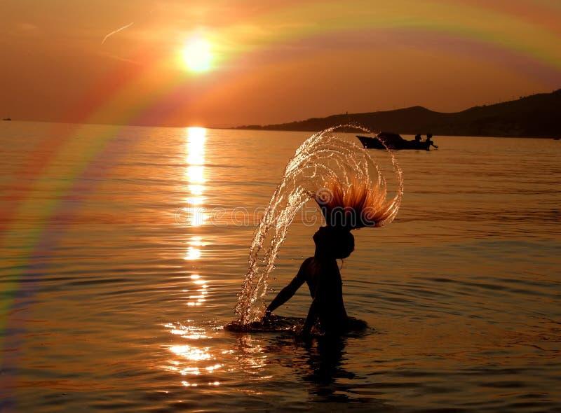 Meisje, boot en regenboog in zonsondergang stock foto
