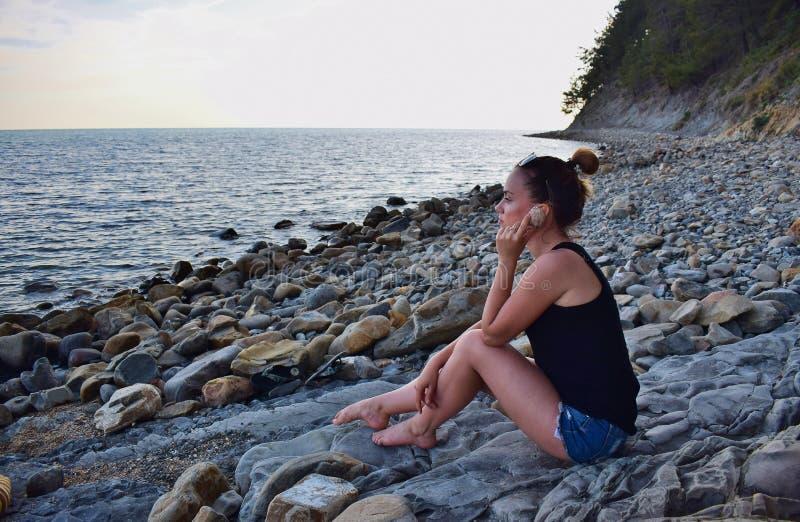 Meisje in borrels en een t-shirt met glazen die op een rotsachtige kust rusten royalty-vrije stock foto's
