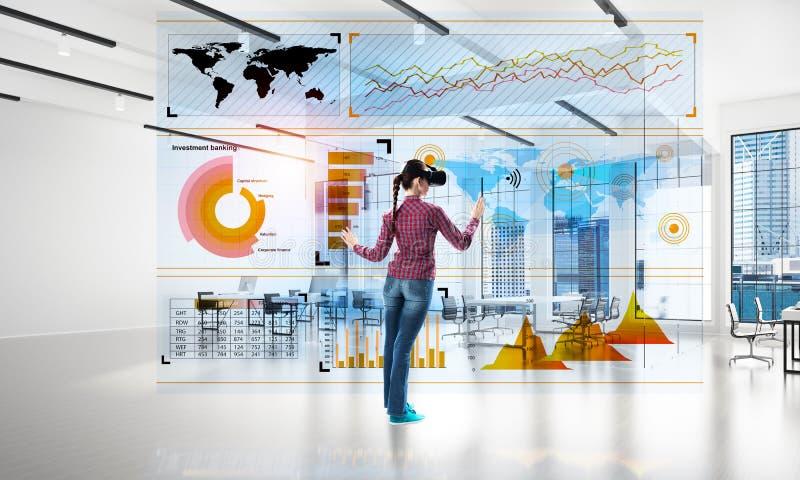 Meisje in bureaubinnenland in virtueel werkelijkheidsmasker die innovatieve technologieën gebruiken Gemengde media stock fotografie