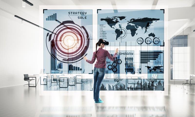 Meisje in bureaubinnenland in virtueel werkelijkheidsmasker die innovatieve technologieën gebruiken Gemengde media stock afbeeldingen