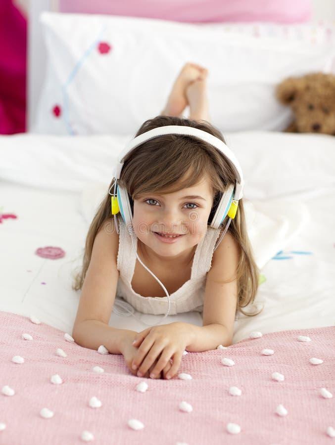 Meisje dat aan de muziek in bed luistert stock foto